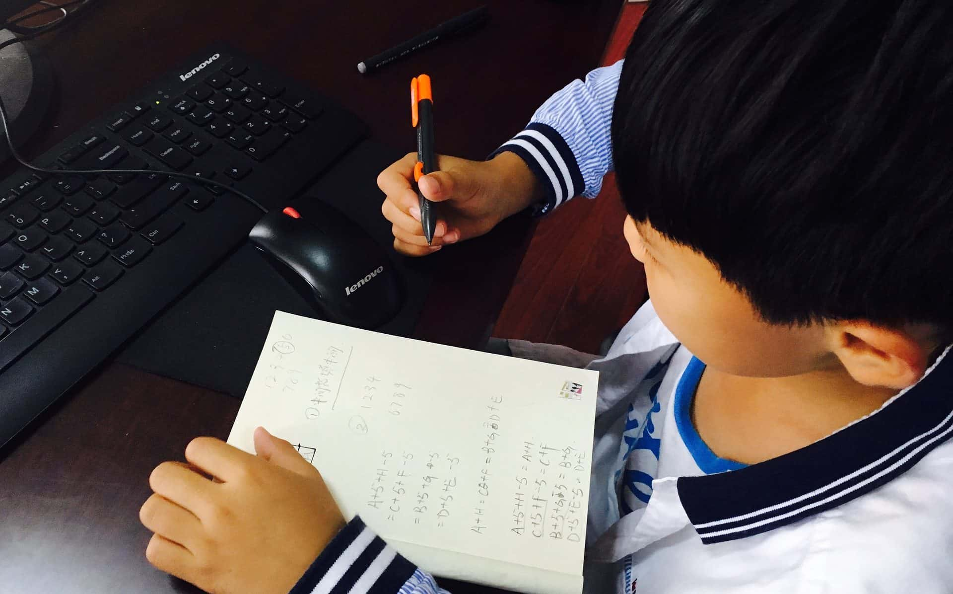 A child writing stuff down on a piece of paper.
