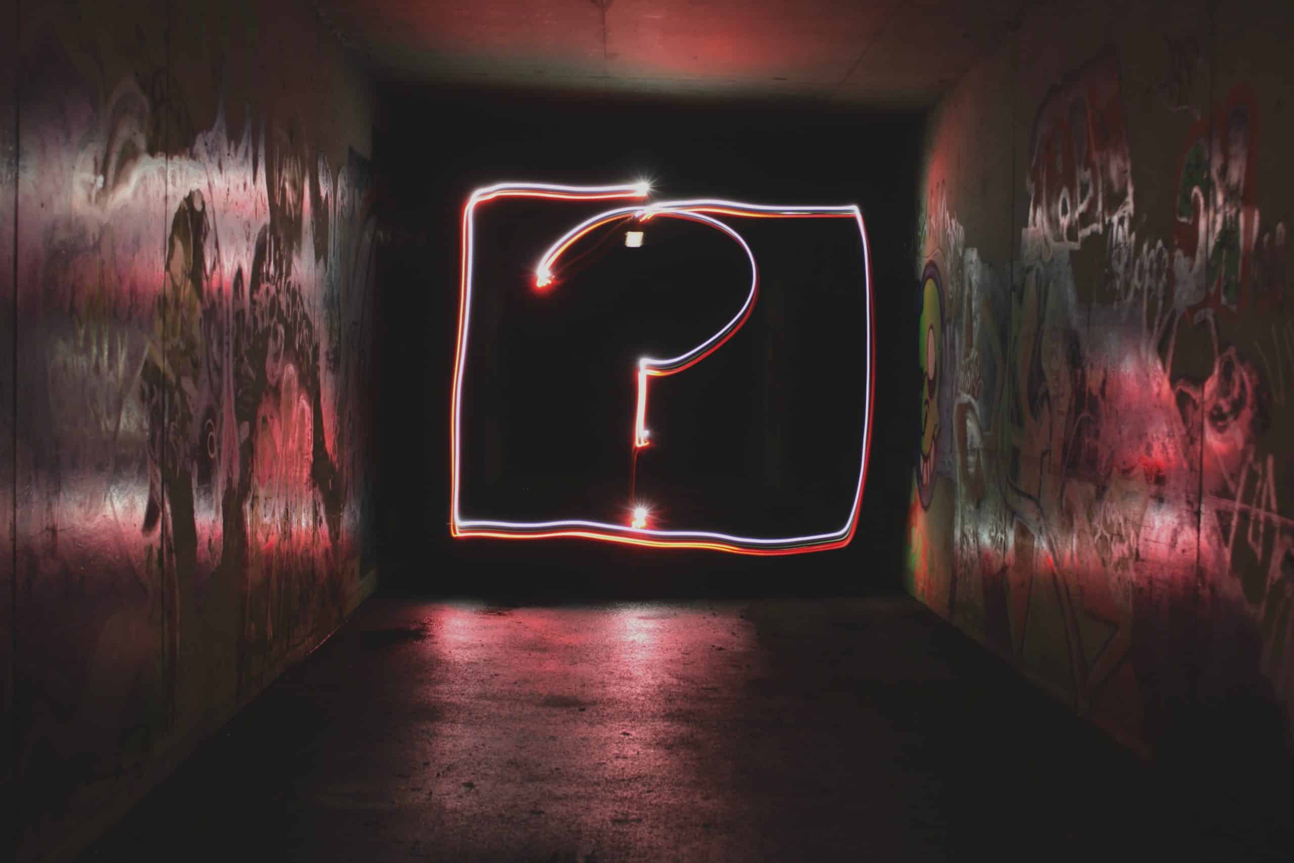 A question mark surrounded by a neon pink box with light illuminating the sides.