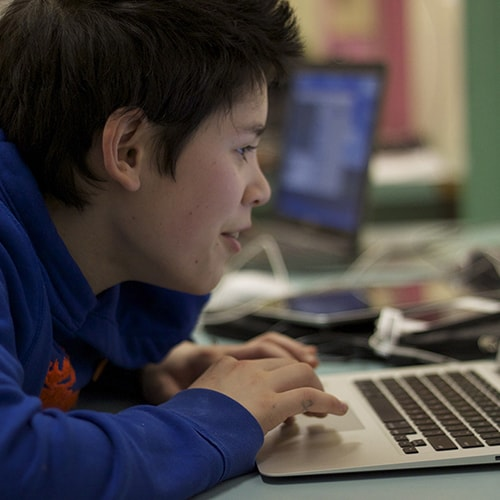 A child using a computer for a lesson.