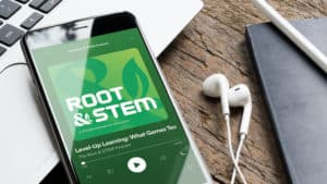 """Smart phone with a set of headphones displaying """"Root & STEM podcast"""" cover art."""