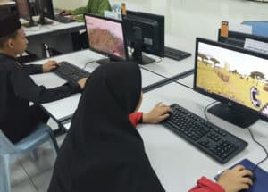 Students playing Minecraft on a computer.