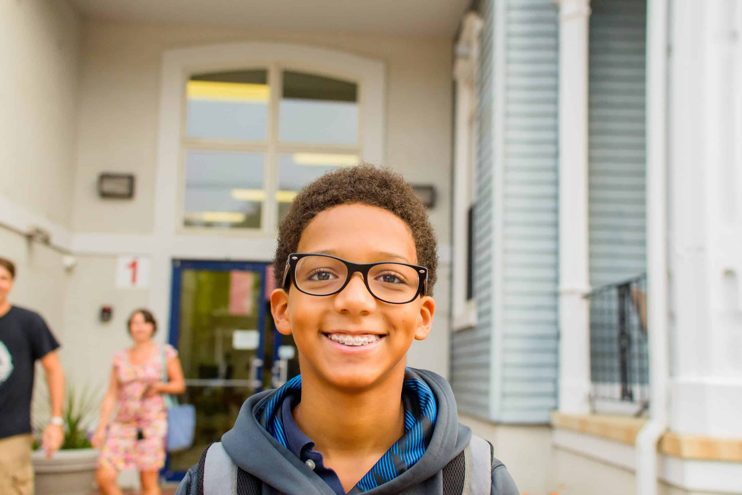 A child smiling in front of a house on the first day of school.